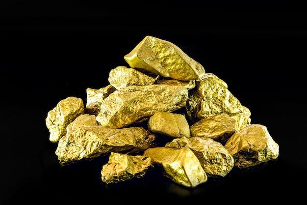 Грубые золотые самородки на черной поверхности