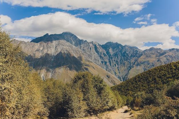 Бурный горный ручей и заснеженные вершины кавказских гор в верхней сванетии, большой кавказский хребет в грузии.