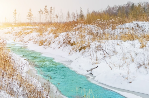 Rough river at the foot of the mountains in a turquoise, blue, green forest in winter, ice and snow around the landscape.