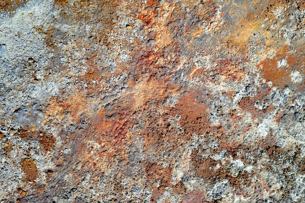 녹슨 빨강 및 회색 반점이 있는 거친 돌 표면. 오래된 구리 광산의 다채로운 질감