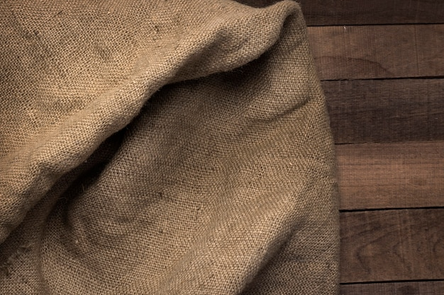 Rough texture of burlap on the background of a wooden table.