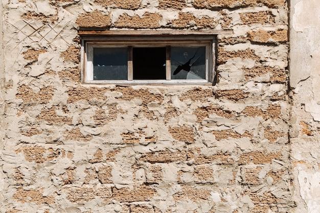 Шероховатая текстура кирпичной стены из ракушек разбитое стекло в жилищных проблемах окна здания