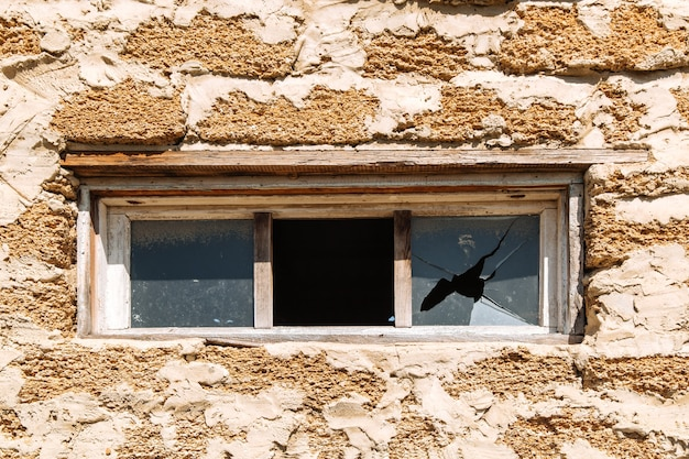 問題を収容する建物の窓のガラスの破片の殻で作られたレンガの壁の粗いテクスチャ