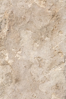Rough, uneven texture of a brown concrete wall close up