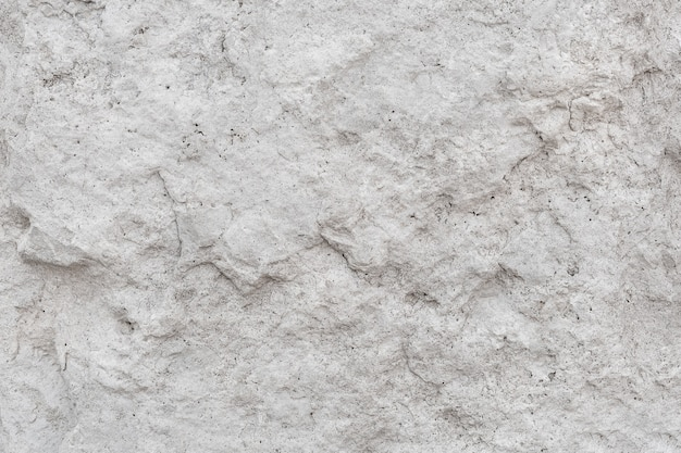Rough uneven texture stone of a gray concrete wall close up