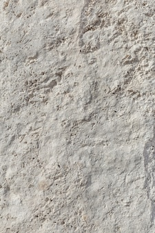 Rough, uneven texture stone of a gray concrete wall close up