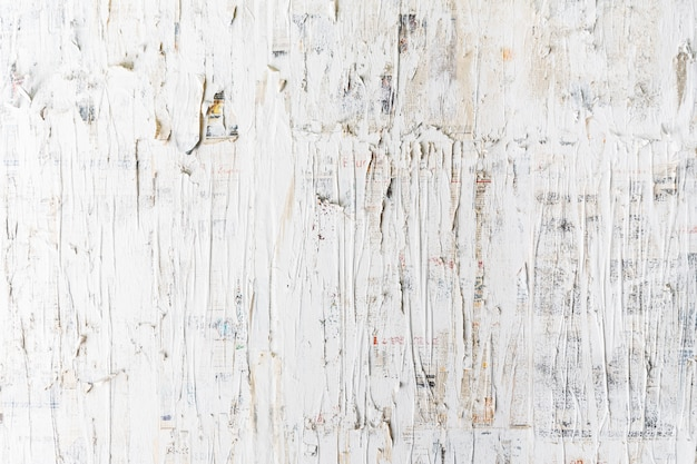 Rough white painted on newspaper wall. perfect for background. abstract  texture. white wallpaper.