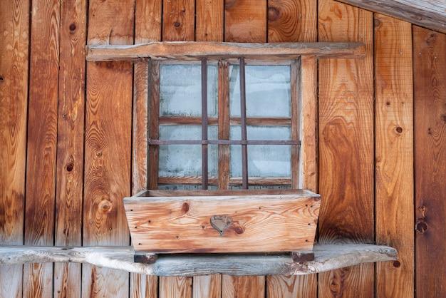 Грубая деревянная стена шале с окном в горах французских альп