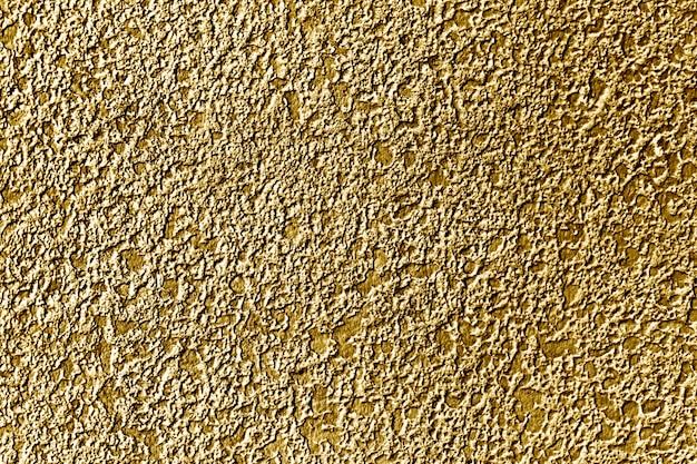 Fondo della superficie del muro di cemento dipinto all'incirca in oro