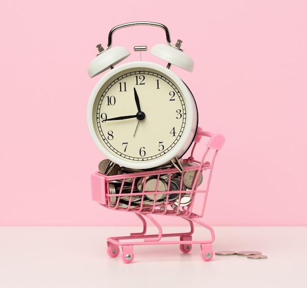 白いテーブルに変更を加えたミニチュアショッピングカートの丸い目覚まし時計。コンセプトタイムはお金、お金の無駄、そして貧困です