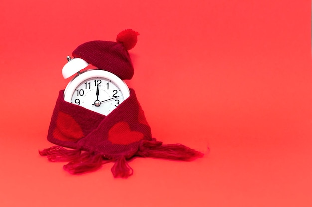 Round alarm clock in knitted red hat and scarf with hearts . on a red background