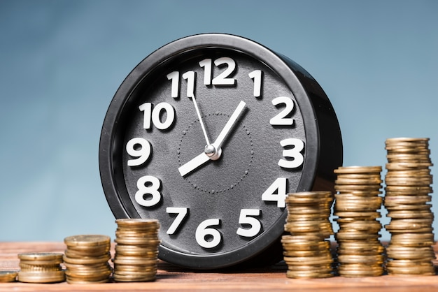 Round alarm clock with stack of increasing coins against blue background