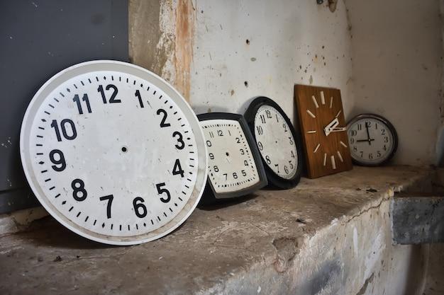 Круглые и квадратные часы у стены, два циферблата, циферблат, множество настенных часов
