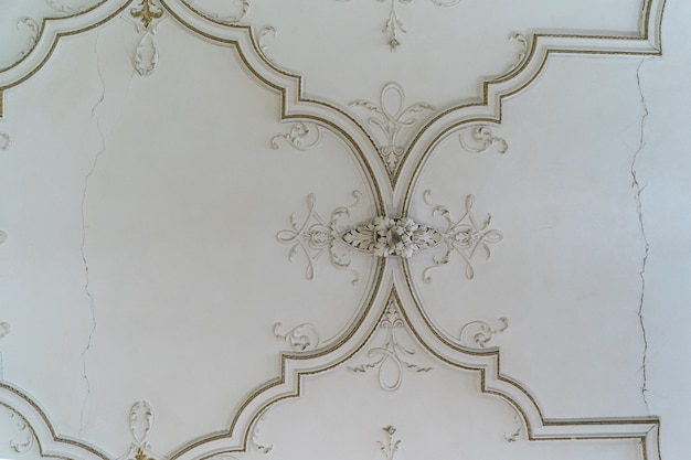 Round antique vintage decorative clay stucco relief molding with floral ornaments on white ceiling in abstract classical style interior
