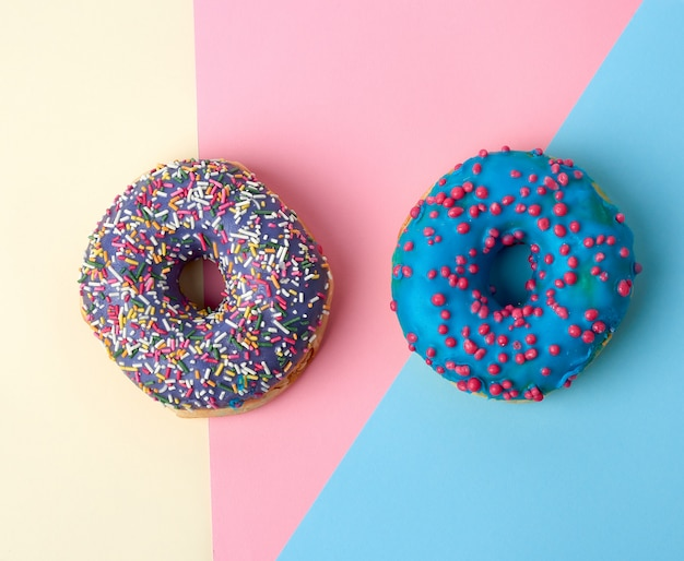 Round baked donut with colored sugar sprinkles and with blue sugar glaze