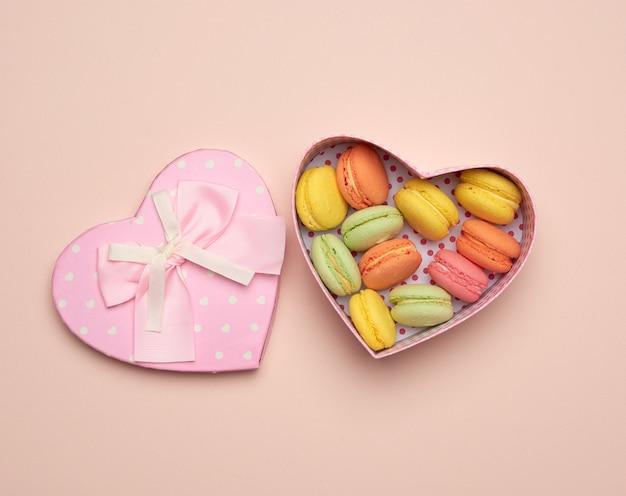 둥근 구운 여러 가지 빛깔의 마카롱이 베이지 색의 심장 모양의 분홍색 골판지 상자에 놓여 있습니다.