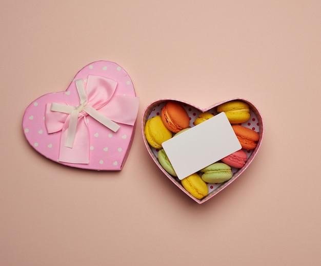 둥근 구운 여러 가지 빛깔의 마카롱이 심장 모양의 분홍색 골판지 상자에 놓여 있습니다.