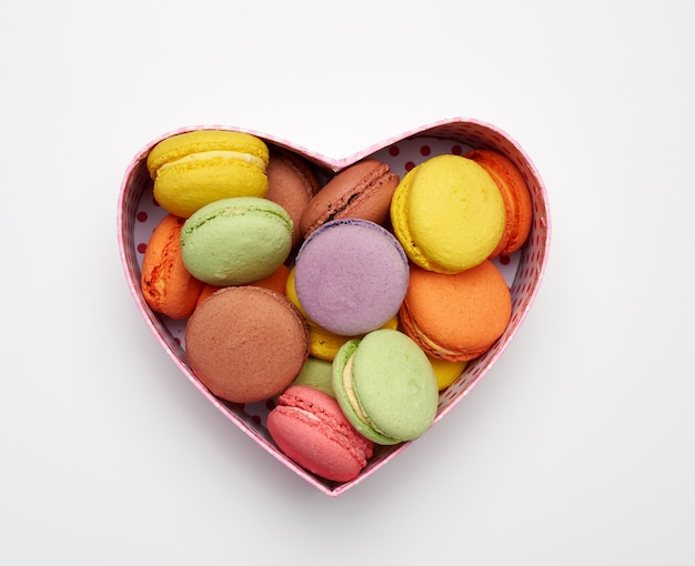 둥근 구운 여러 가지 빛깔의 마카롱이 심장 모양의 빨간색 골판지 상자에 놓여 있습니다.