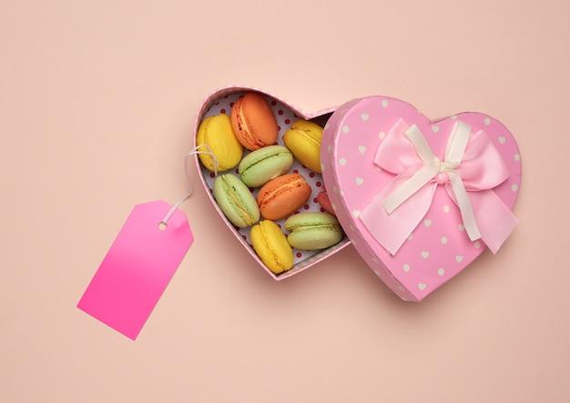 Круглые запеченные разноцветные макаруны в розовой картонной коробке в форме сердца