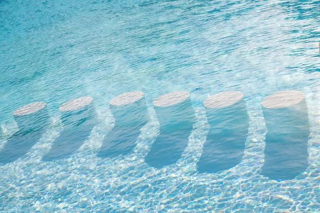 물 배경 아래 라운드 바 의자 수영장에서 맑은 청록색 물
