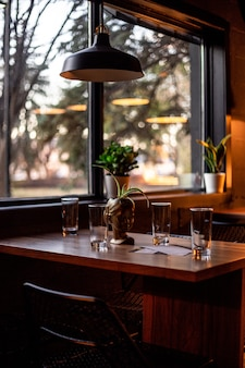 갈색 나무 테이블과 둥근 흑백 펜던트 램프에 둥근 기본 투명 음주 안경