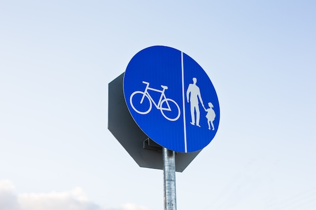 Круглый знак велосипедной дорожки против голубого неба