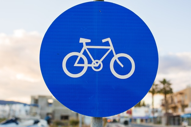 Round bicycle lane sign against a blue sky