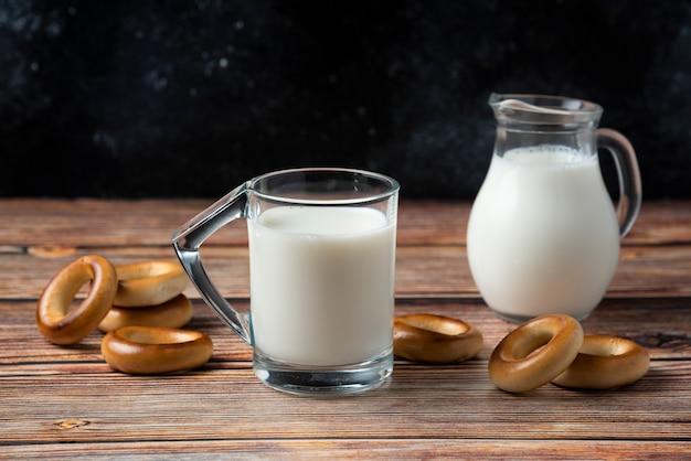 Biscotti rotondi, tazza di vetro e brocca di latte sulla tavola di legno.