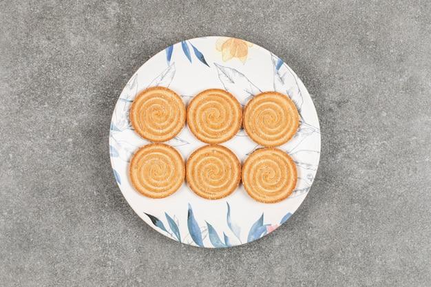 화려한 접시에 참 깨와 라운드 비스킷