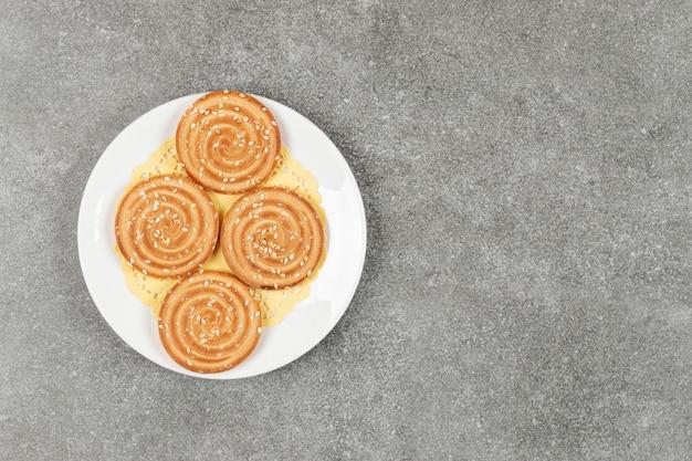 흰색 접시에 참 깨와 라운드 비스킷