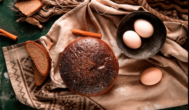 Round black bread with slices, cinnamon and egg bowl on a green table.