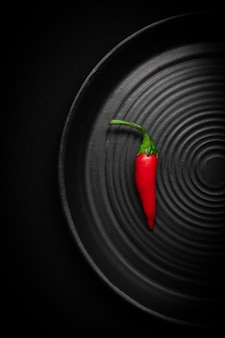 Round black ceramic plate with pattern of circles with red fresh chili pepper