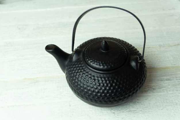 A round and black kettle on a wooden table
