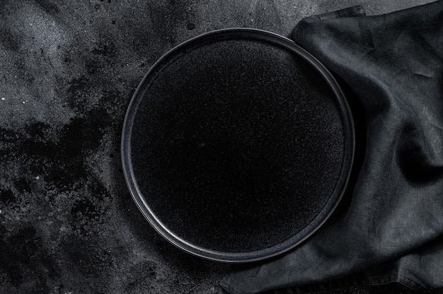 織り目加工の黒い背景に丸い黒いプレート