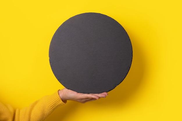 Круглая черная грифельная доска под рукой над желтым, пустое место для меню или рецепта.