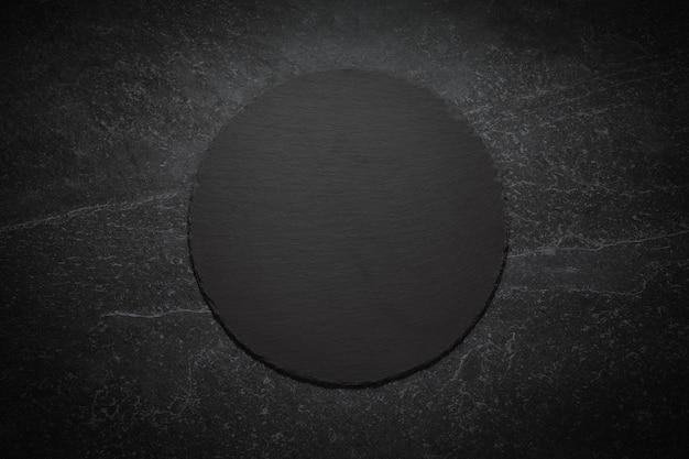 Круглая черная шиферная доска на мраморном фоне, изображение с пространством для текста