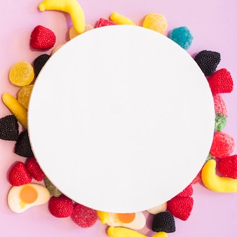Round blank frame over the colorful candies on pink backdrop