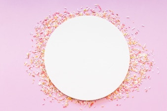 Round blank white frame surrounded with sprinkles on pink background