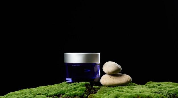화장품용 뚜껑이 있는 둥근 파란색 유리 항아리는 녹색 이끼, 검은 배경에 서 있습니다. 천연 크림과 마스크. 제품 브랜딩