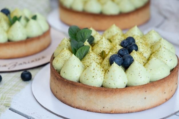 창가에 녹색 피스타치오 크림과 딸기 잼을 곁들인 라운드 블루 베리 파이