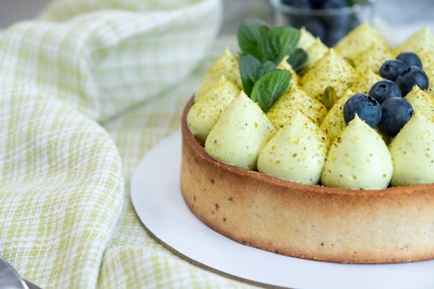 녹색 피스타치오 크림과 딸기 잼을 곁들인 라운드 블루 베리 파이 피스타치오 파이