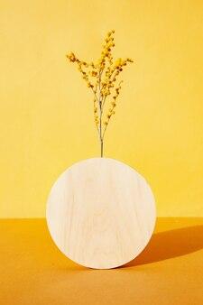 Круглая доска с веточками возле цветущего растения