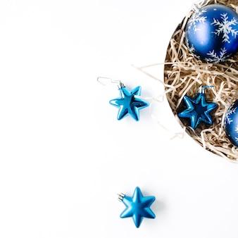 白い背景の上の明るい青いクリスマスボールと丸いボックス。