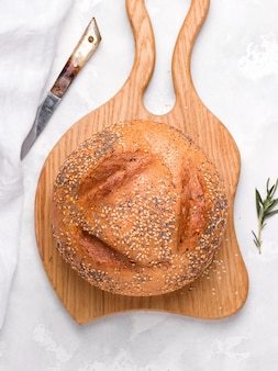 Круглый хлеб на деревянной доске. вертикальное фото