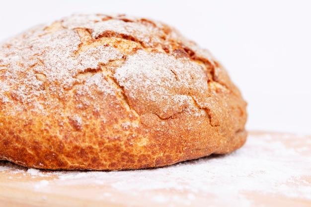 나무 보드에 바삭한 빵 껍질을 가진 둥근 빵. 확대.