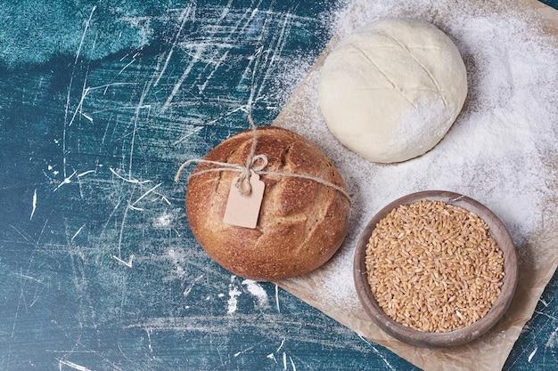 青いテーブルの上に小麦と生地の丸いパン。