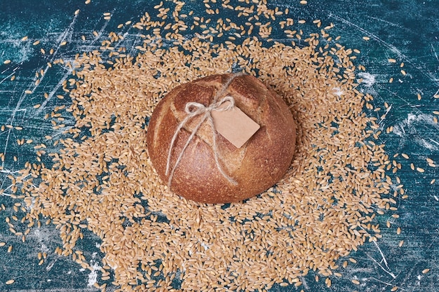 Round bread with wheats on blue table.