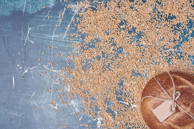 青いテーブルの上の小麦と丸いパン。