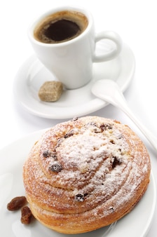Round bun with raisins and cup of coffee on white background