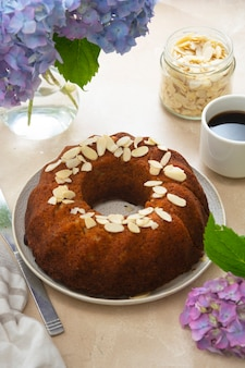 Round bundt cake, homemade pastry cake with coffee cup and flowers on background